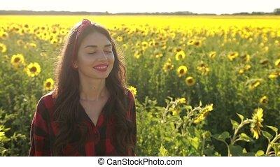 Happy woman walking in fresh sunflower field