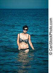 Happy woman walking in sea