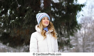 happy woman walking in winter forest or park