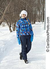 Happy woman walking in winter park