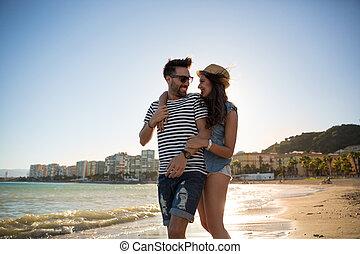 Happy woman walking on beach with boyfriend embracing him