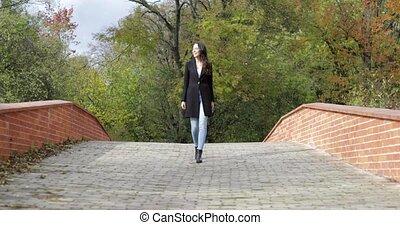 Happy woman walking on bridge - Happy-looking woman in black...