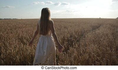 Happy woman walking on golden wheat field