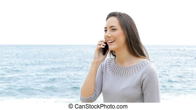 Happy woman walking and talking on phone on the beach with the sea in the background
