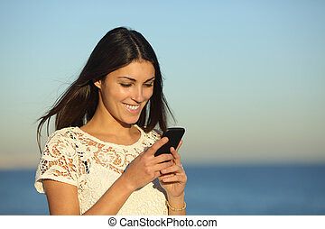Happy woman walking using a phone on the beach