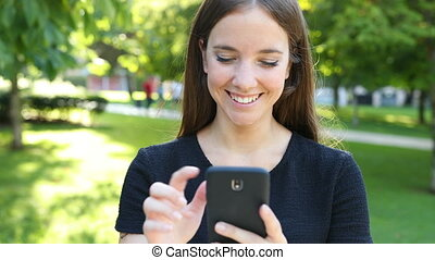 Happy woman walks in a park using phone