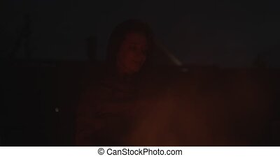 Tourist girl sitting by fire burning outdoors in evening black background slow motion. Real people snapshot summer vacation