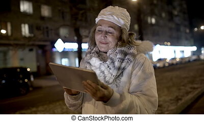 Happy woman watching something on pad during evening walk