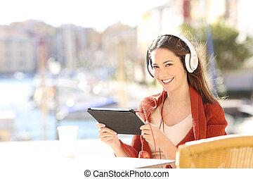 Happy woman watching videos looking at camera