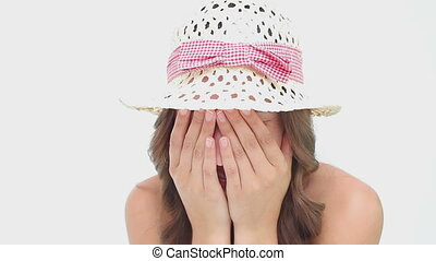 Happy woman wearing a hat while hiding her face against a white background