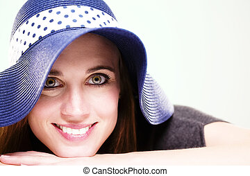 happy woman wearing a summer hat on light green background