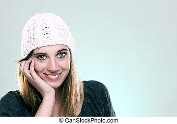 happy woman wearing a winter cap on light blue background