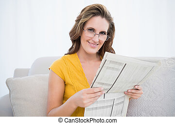 Happy woman wearing glasses holding newspaper