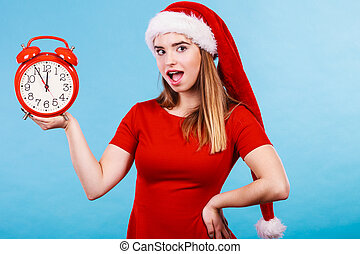 Happy woman wearing Santa Claus costume holding clock