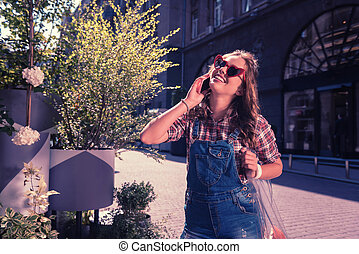 Happy woman wearing stylish casual clothes speaking by phone with her friend