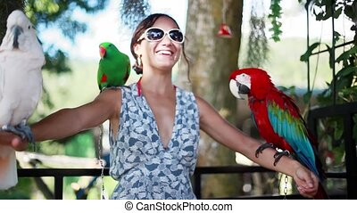 Happy woman wearing sunglasses holds parrots blue-gold...