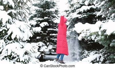 Happy woman whirls in a snowy forest and falls to the snow...