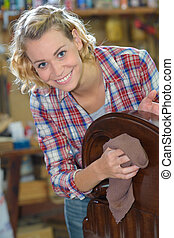 happy woman wiping the dust from wooden furniture