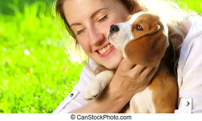 happy woman with a dog beagle playing on nature