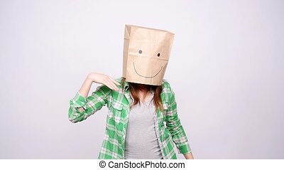Happy woman with a paper bag on her head dancing