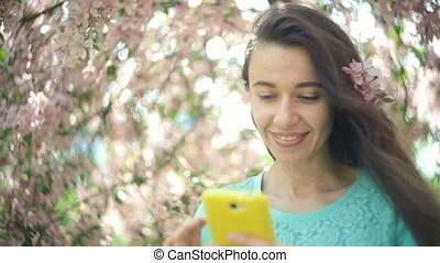 Happy woman with a phone in a blooming spring garden