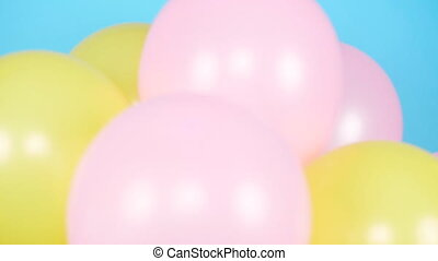 Happy woman with an air colorful balloons is having fun on a blue background