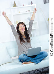 happy woman with arms up and laptop