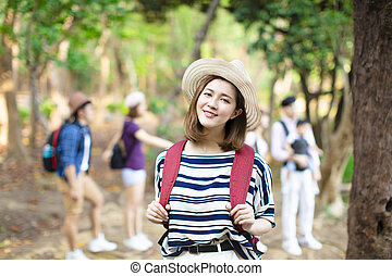 happy woman with backpack hiking in  forest