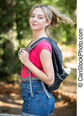 happy woman with backpack in the forest
