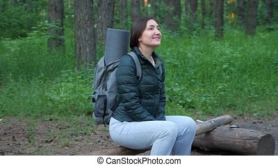 Happy woman with backpack sitting on a log in the forest.
