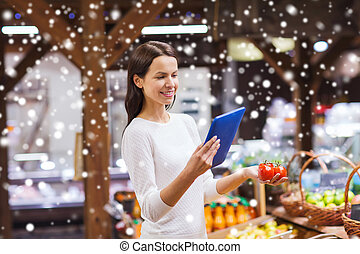happy woman with basket and tablet pc in market