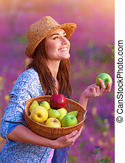 Portrait of happy woman with basket of apples on pink floral field, enjoying tasty ripe fruits, working in garden, harvest concept