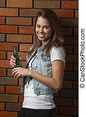 Happy woman with beer - twenty something girl leaning...