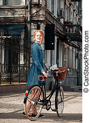 Happy woman with bicycle standing on the street