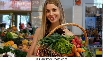 Happy woman with big basket at the market