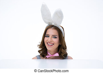 Happy woman with bunny ears sitting at the table and looking at camera