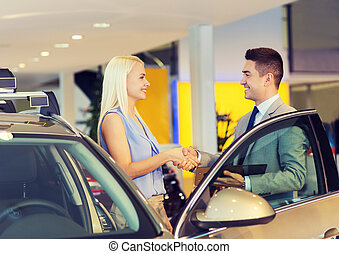 happy woman with car dealer in auto show or salon