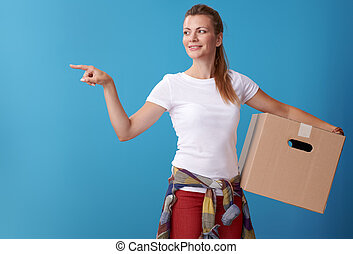 happy woman with cardboard box pointing at something on blue