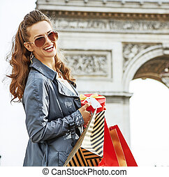 happy woman with Christmas present near Arc de Triomphe in Paris