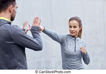happy woman with coach working out strike outdoors