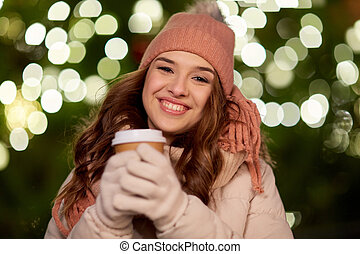 happy woman with coffee over christmas lights - winter...
