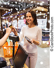 happy woman with credit card buying food in market
