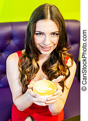 Happy woman with cup of coffee in hands