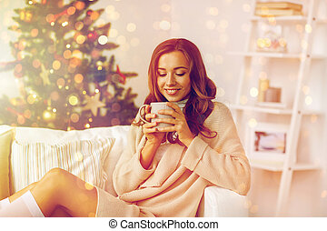 happy woman with cup of tea at home for christmas