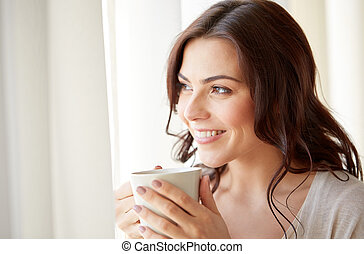 happy woman with cup of tea or coffee at home