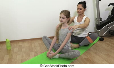 Happy woman with daughter doing yoga in living room