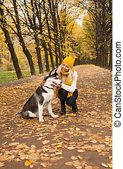 Happy woman with dog hugging outdoor