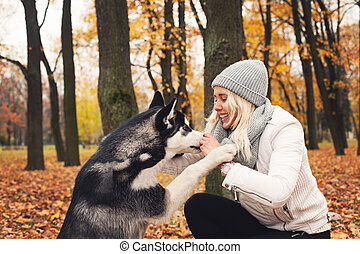 Happy woman with dog husky outdoors in the autumn park