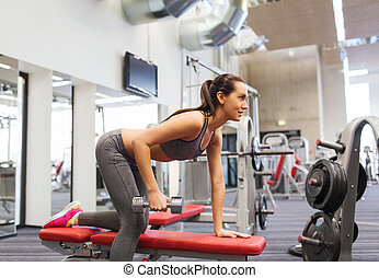 happy woman with dumbbell flexing muscles in gym - fitness, ...