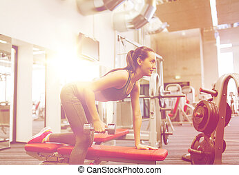 happy woman with dumbbell flexing muscles in gym